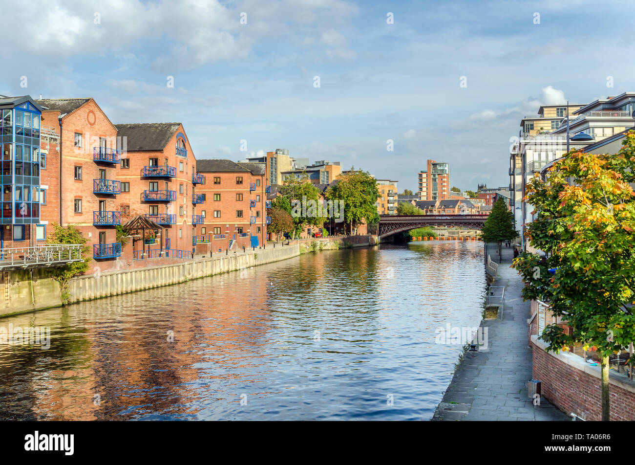 Renovated warehouses along a river on a sunny autumn day - Stock Image