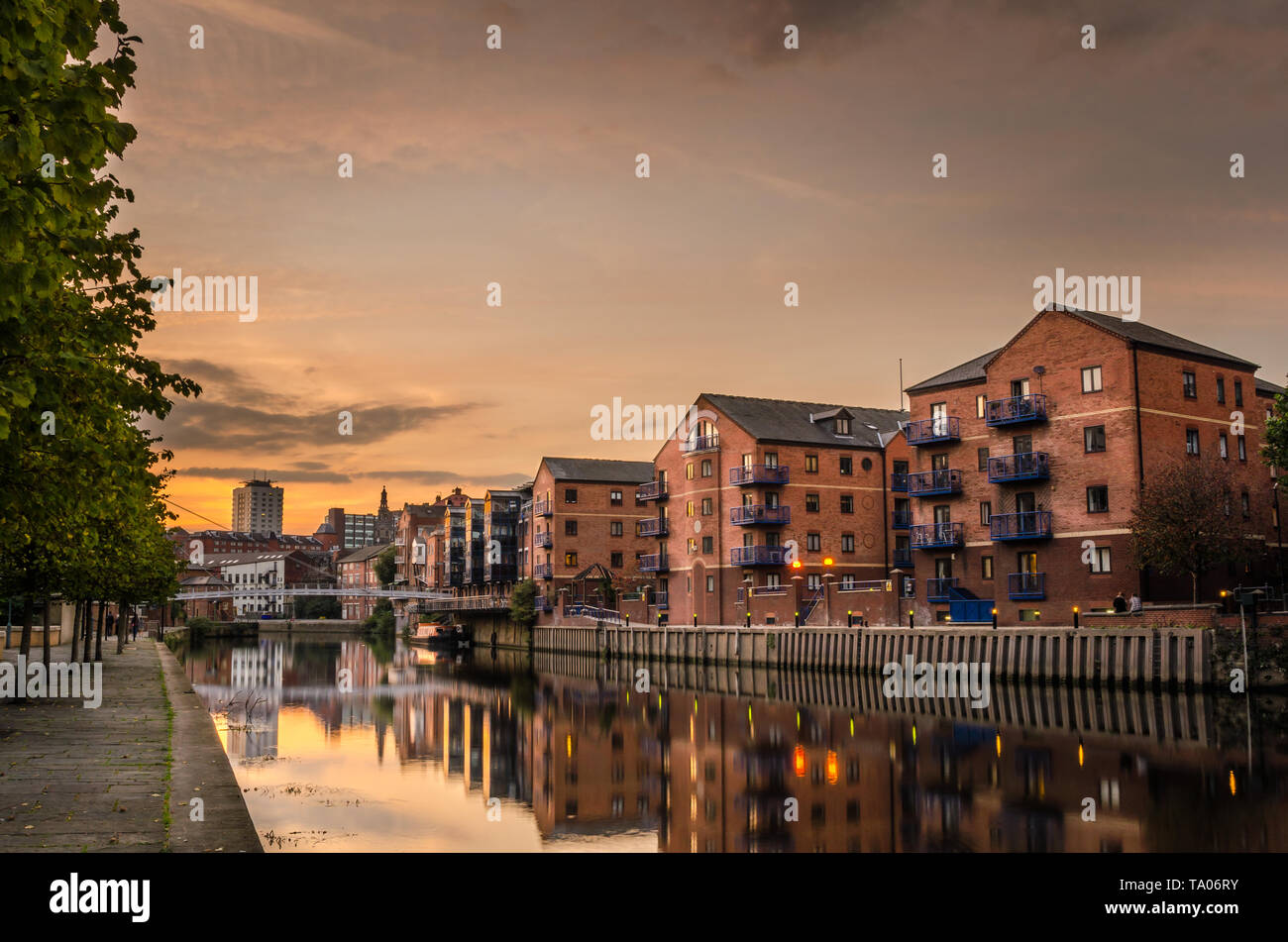 Brick apartment buildings and renovated warehouses along the river Aire in Leeds at Sunset. Reflection in water. Stock Photo