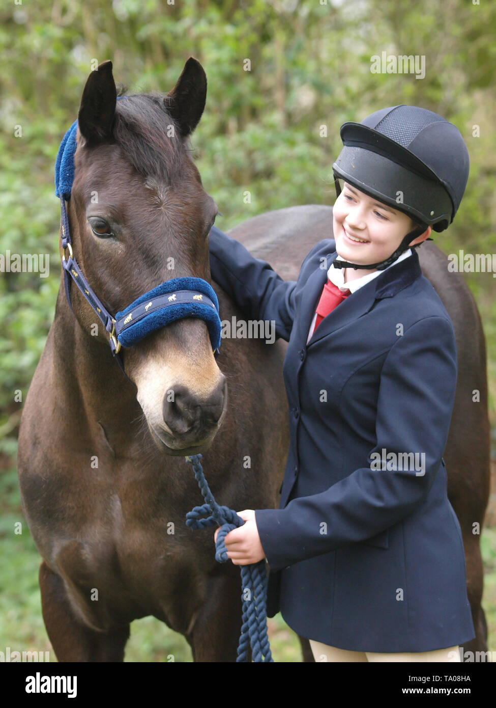 A young girl stands next to her favourite bay horse. - Stock Image