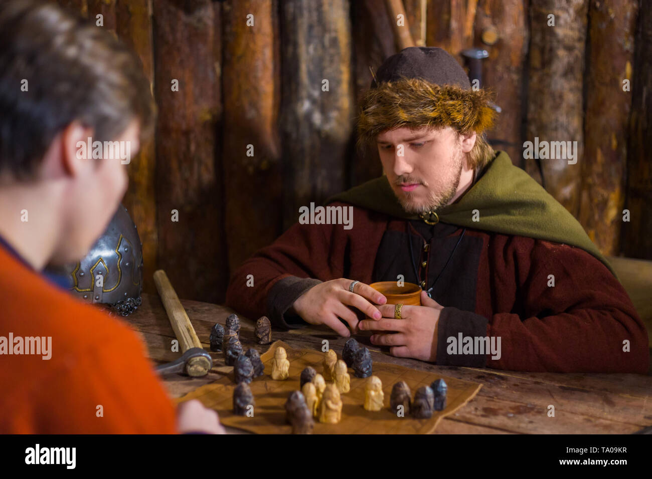 Portrait of man in russian ethnic suit playing board game like chess. Folk, competition and traditional concept - Stock Image