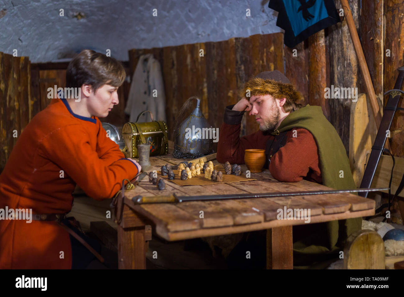 Two men in russian ethnic suit playing medieval popular strategy board game - tafl. Folk, competition and traditional concept - Stock Image