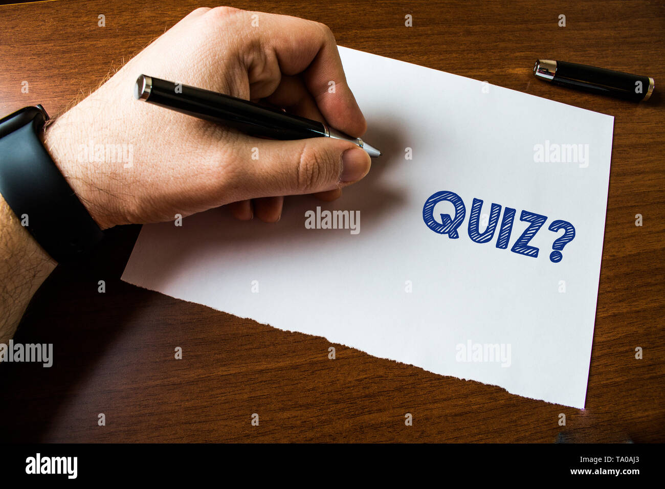Conceptual hand writing showing Quiz Question. Concept meaning test of knowledge as competition between individuals or teams Man left hand watch paper - Stock Image