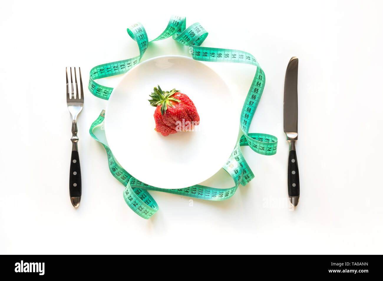 White table setting with tape measure and one organic ugly strawberry. Concept weight loss for Detox. View from above. - Stock Image