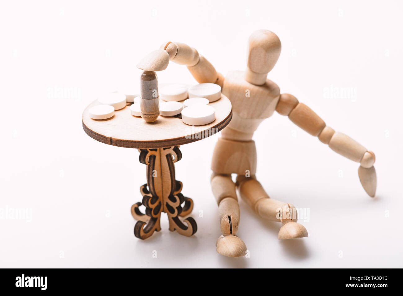Medication regimen. Human wooden dummy near table with medicines. Tips tackling complex medication regimen. Take medicines after food. Health care and medical treatment. Pills on tiny wooden table. - Stock Image