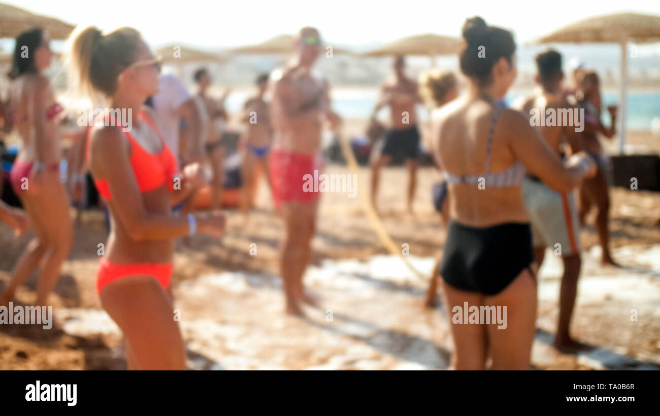 Defocused image of big group of people dancing on the sea beach disco party. People having fun during summer holiday vacation - Stock Image