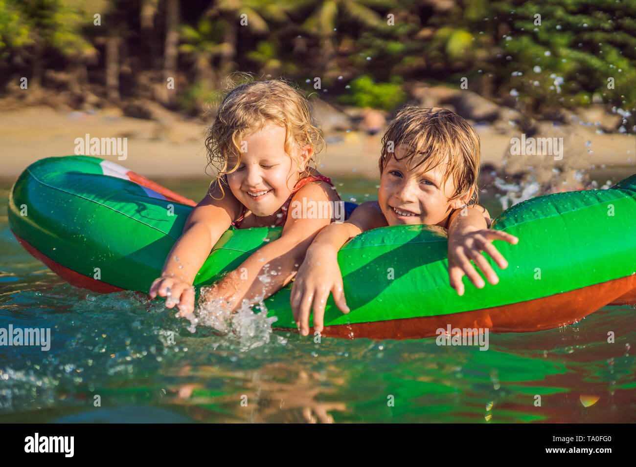 Children swim in the sea on an inflatable mattress and have fun Stock Photo