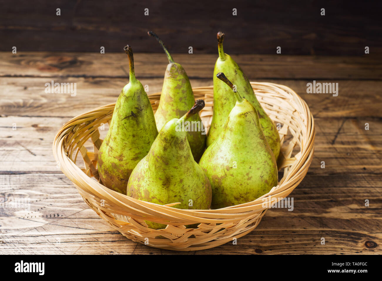 Fresh juicy Pears Conference in a basket on a wooden rustic background - Stock Image