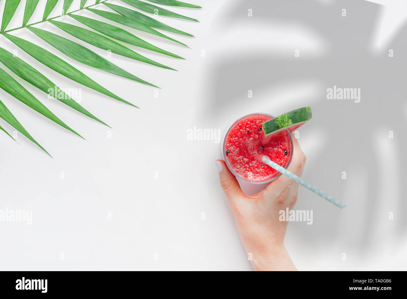 Creative scandinavian style flat lay top view of fresh watermelon slices smoothie drink in glass woman hands on white table background copy space. Min - Stock Image