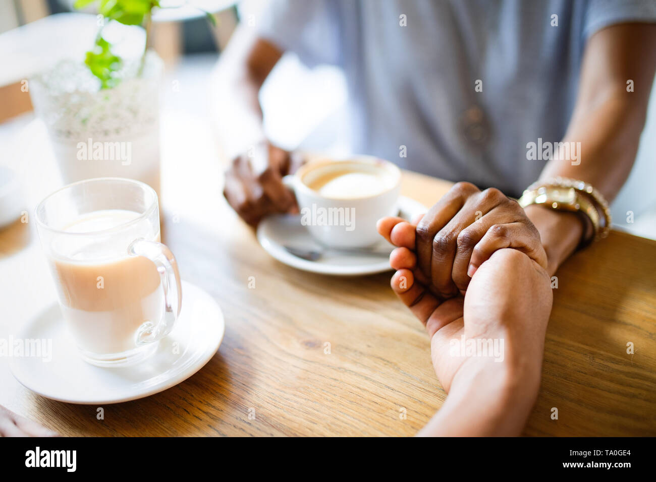 Close-up of couple holding hands while sitting together in cafe with coffee cups on the table - Stock Image