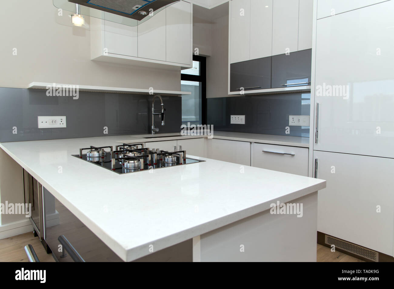 A white marble kitchen counter top with a gas stove built in ...