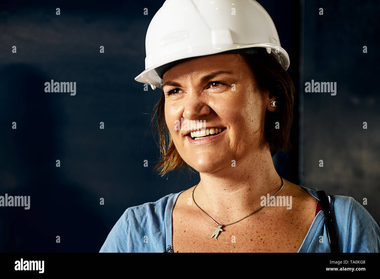 Beautiful portrait of a female project manager wearing a hard hat during an on site visit at the construction site - Stock Image