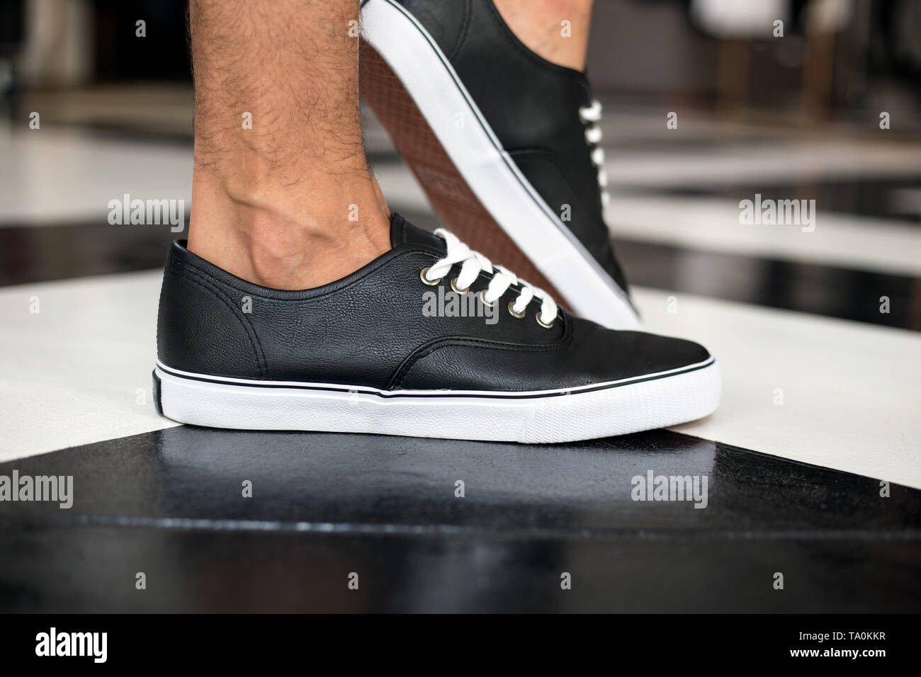 A simple style of black and white leather sneakers on feet for men. - Stock Image