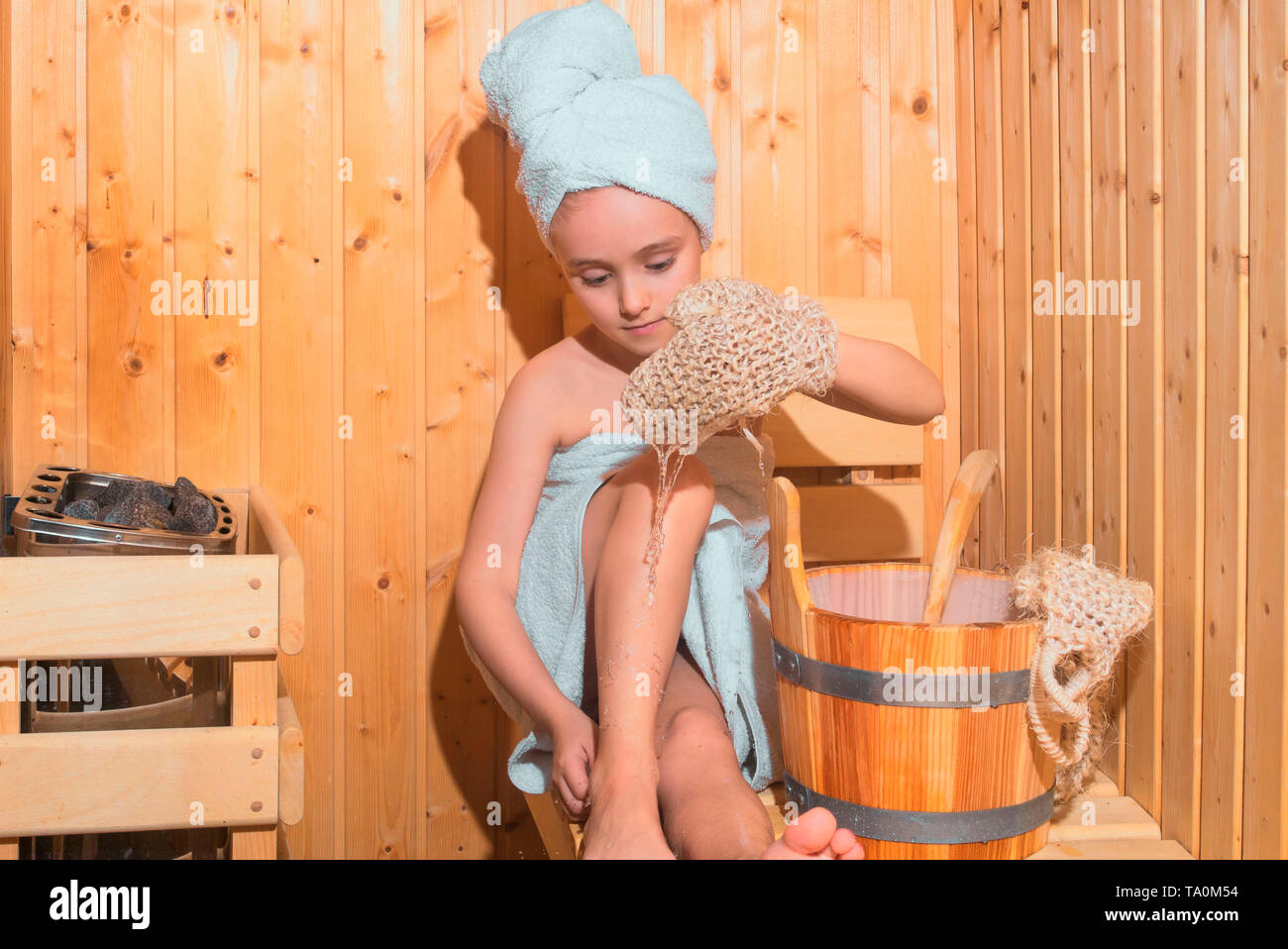 Young Girl relaxing in sauna,girl in a spa treatment in a traditional sauna with a brush for skin and a washcloth. - Stock Image