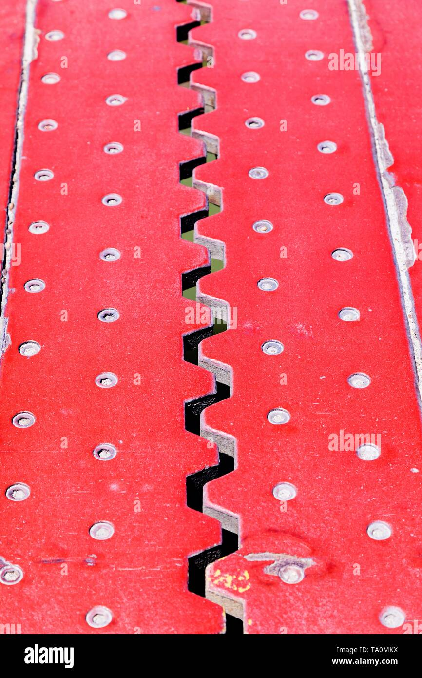 Top view from above of an red iron dilatation joint placed on a opening bridge road - Zigzag line from steel - Stock Image