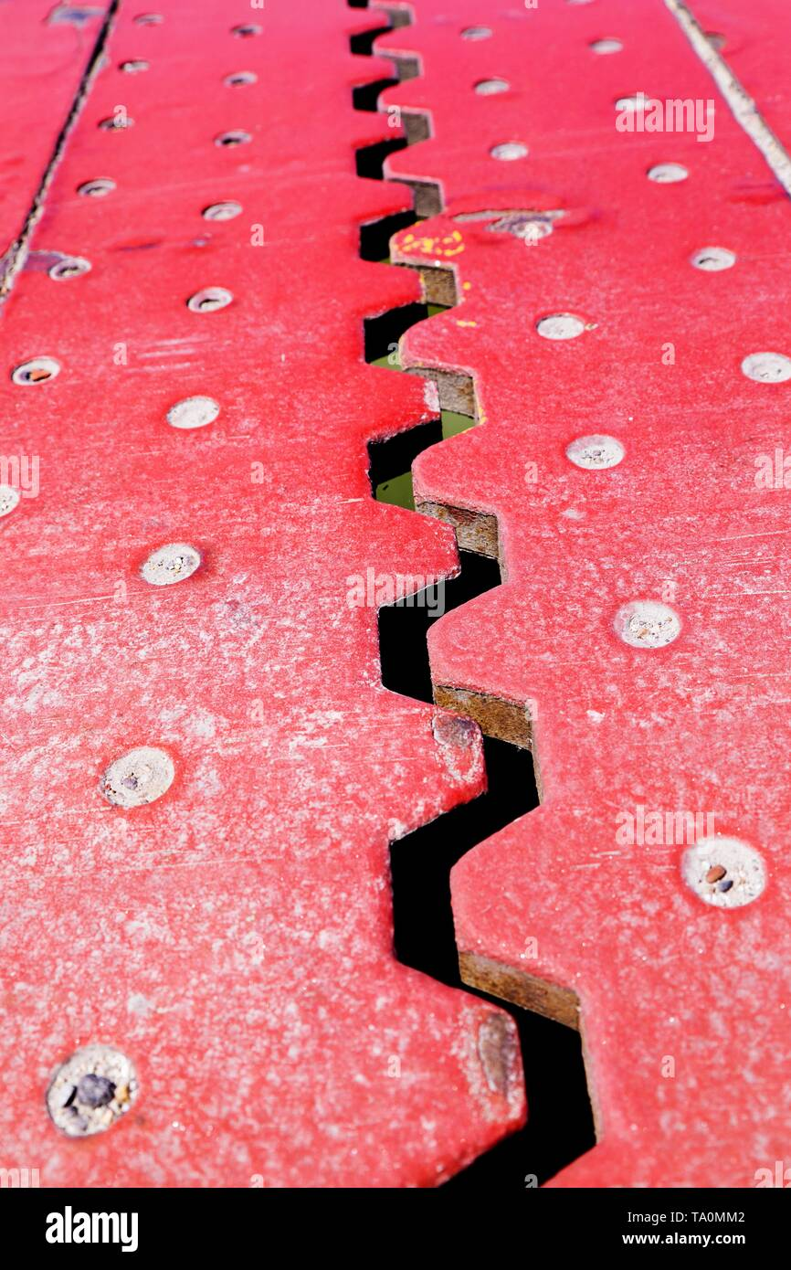 Close up view from above of an red iron dilatation joint placed on a opening bridge road - Zigzag line from steel - Stock Image