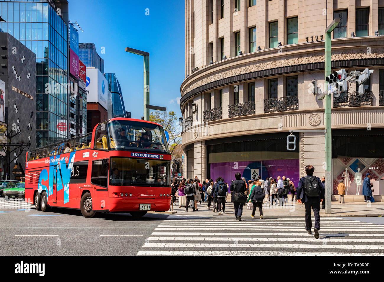 3 April 2019: Tokyo, Japan - Sky Bus Tokyo, a red open top double decker tour bus, sightseeing in the Ginza districtm stopped at a road crossing. Stock Photo