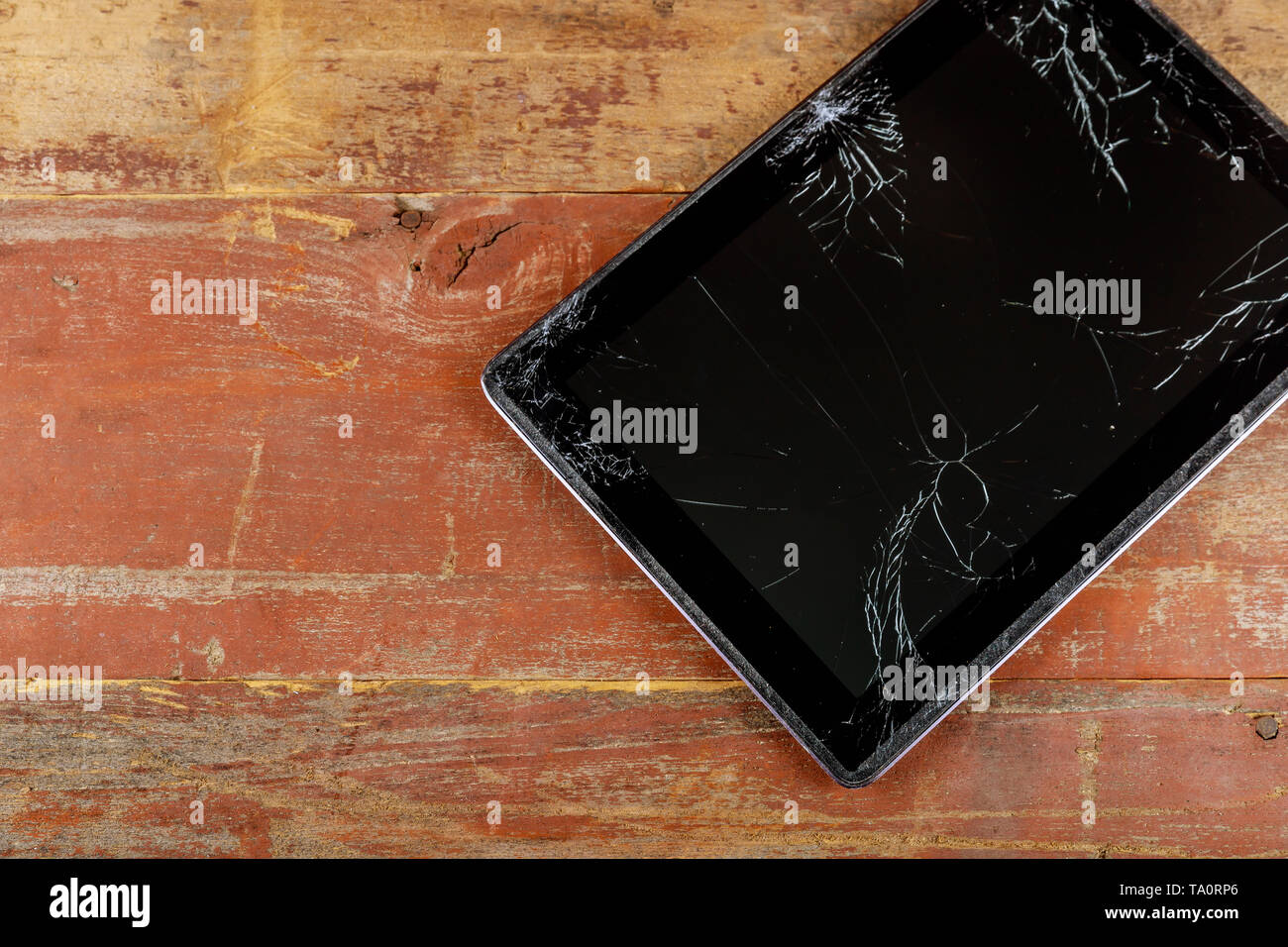 Digital tablet with broken glass screen on the wood background - Stock Image