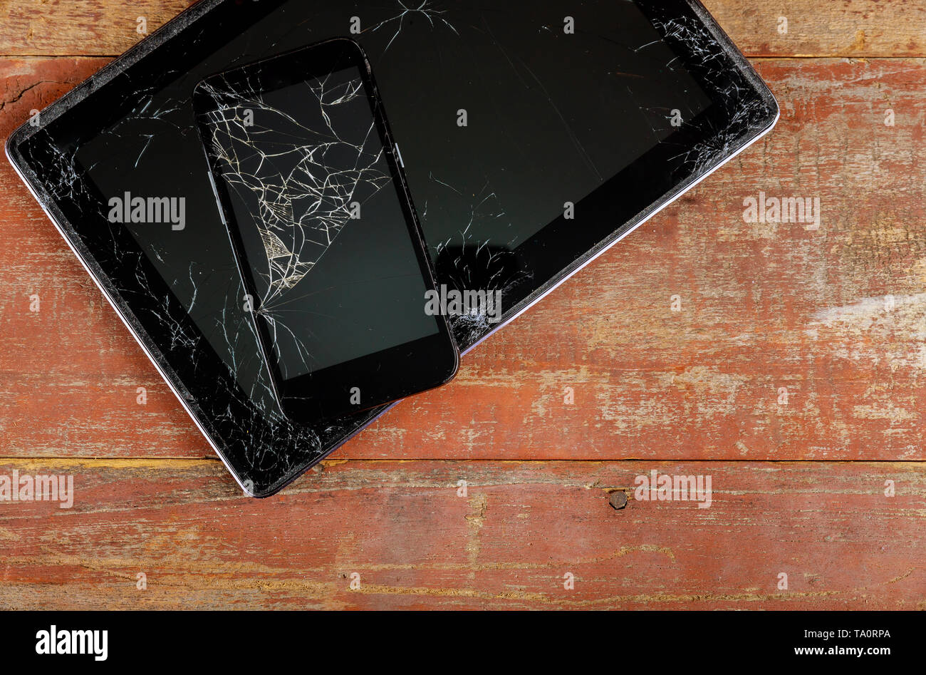 Tablet computer and smart phone with broken glass screen on the wood background - Stock Image