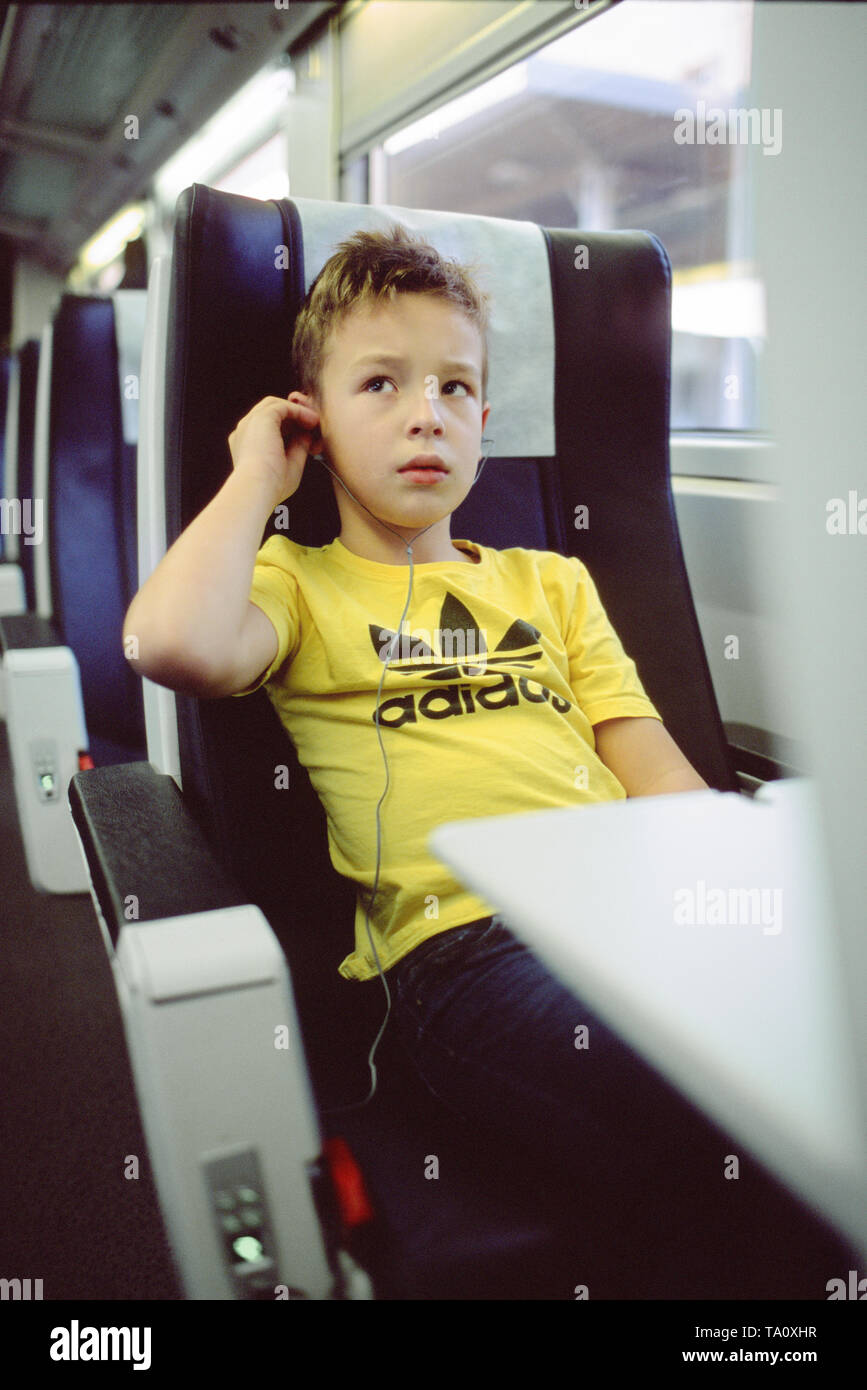 Child with earbuds in train - Stock Image