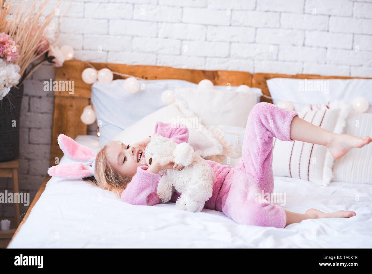 Smiling baby girl 4-5 year old lying in bed with teddy bear in room. Good morning. Childhood. - Stock Image