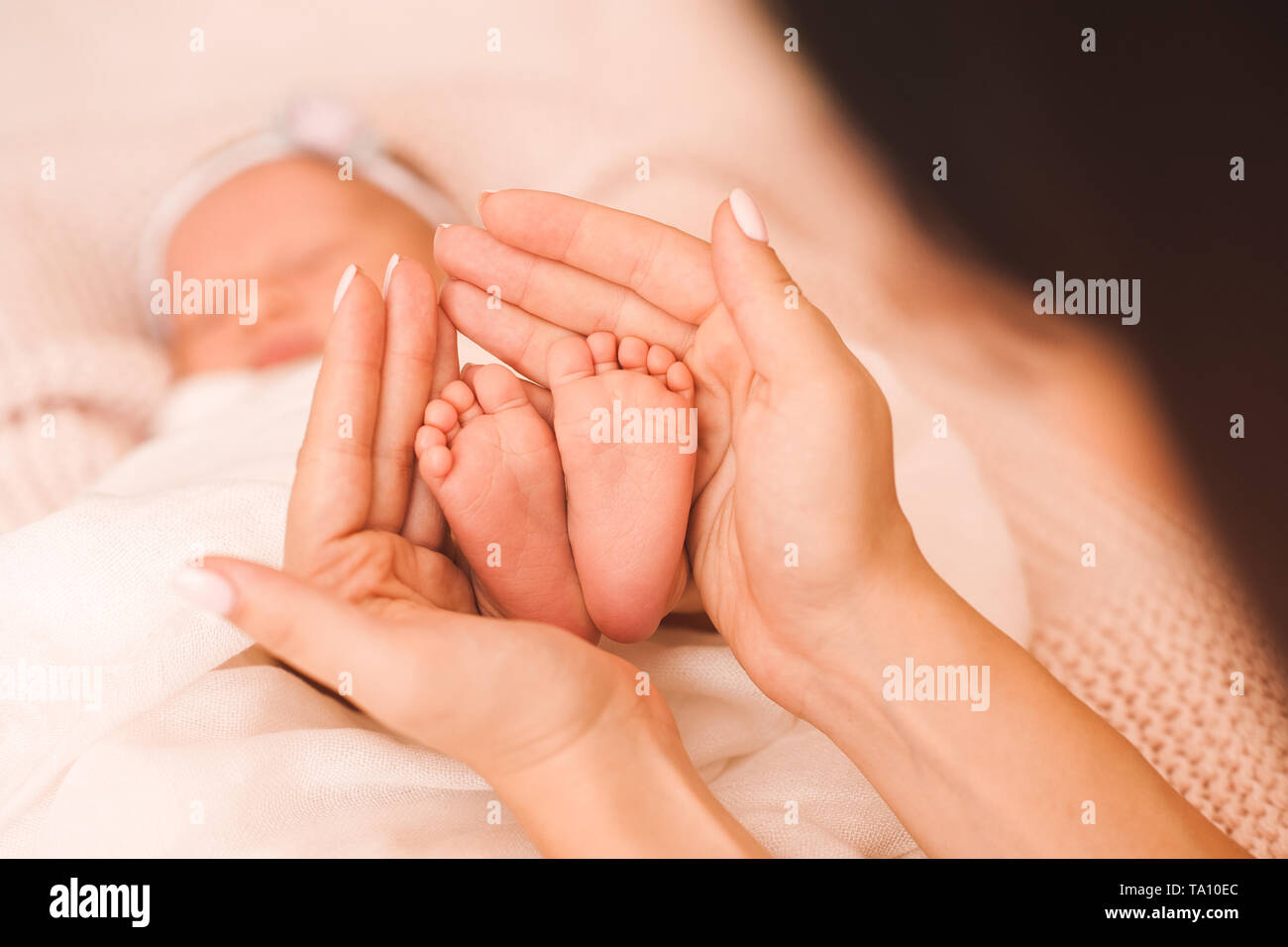 Woman holding baby feet in bed closeup. Maternity. Motherhood. - Stock Image