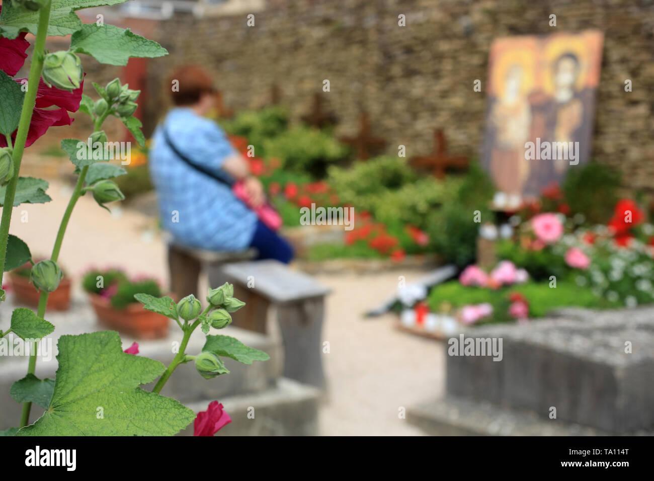 Pèlerin priant devant la tombe de Frère Roger. Taizé. - Stock Image
