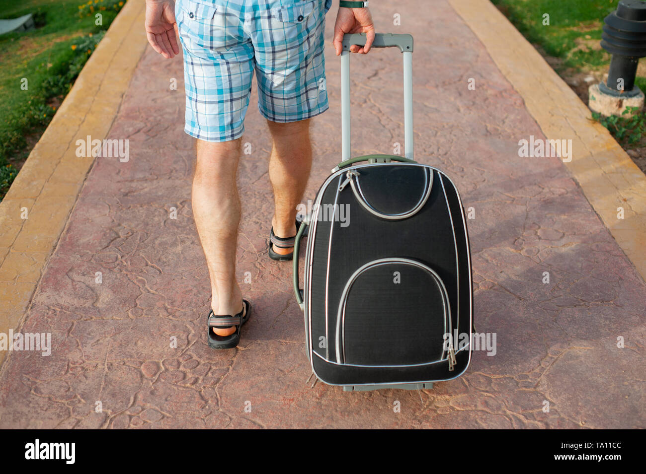 Young man pulling suitcase on road in summer park. Travelling guy wearing smart shorts walking away with his luggage - Stock Image
