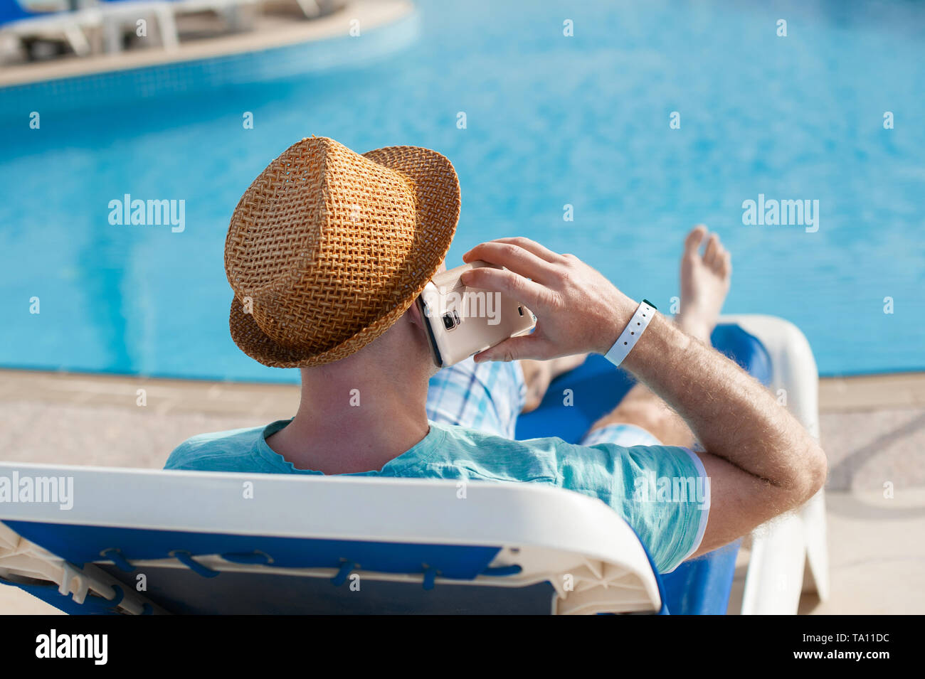 man lying on a lounger and talking on a phone near the pool - Stock Image