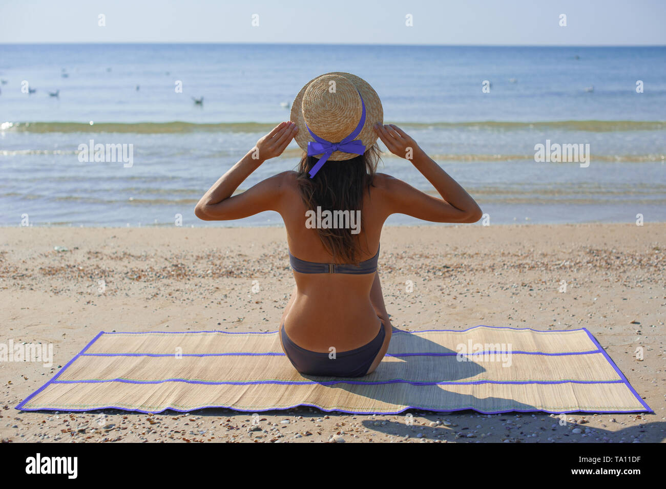 Beach holidays woman enjoying summer sun sitting in sand looking happy at copy space. Beautiful young model - Stock Image