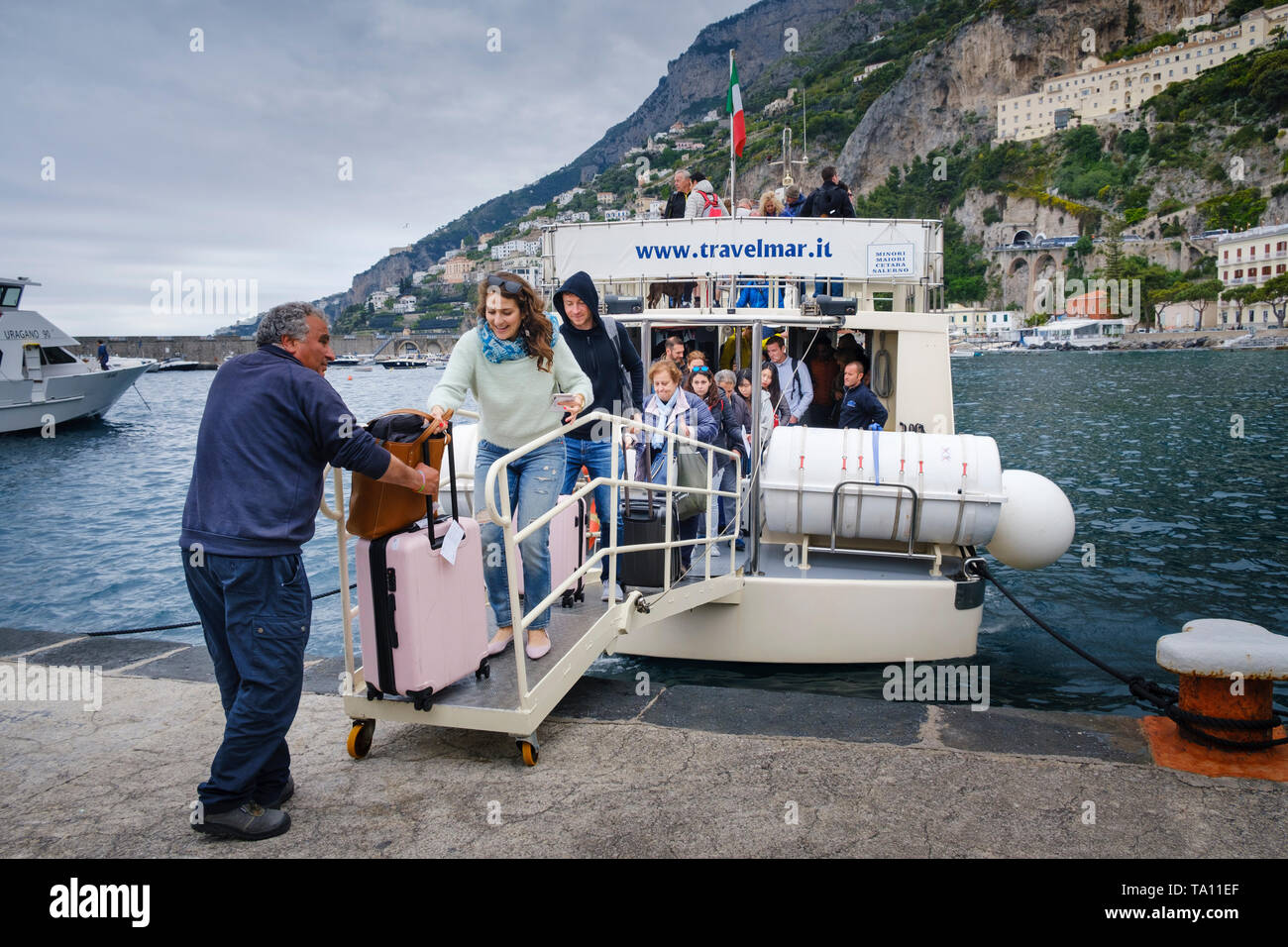 Boat transport. Woman tourist with luggage and other passengers disembarking from a Travelmar Ferry at the harbour in Amalfi on the Amalfi Coast. - Stock Image