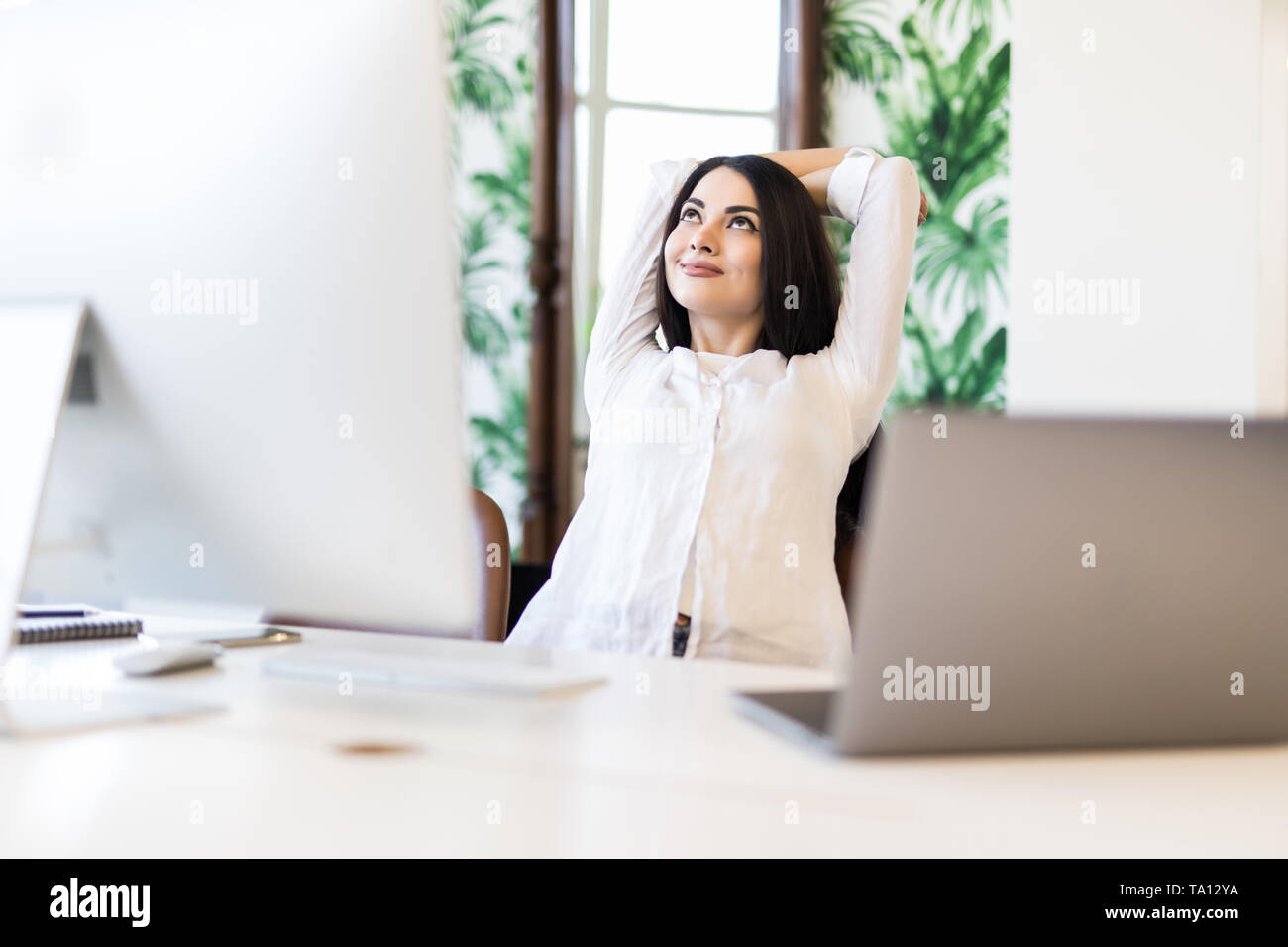 Cheerful woman sitting at desk with hands behind head. Business lady imagines happy future with closed eyes. Relaxed girl resting in office chair. Gre - Stock Image