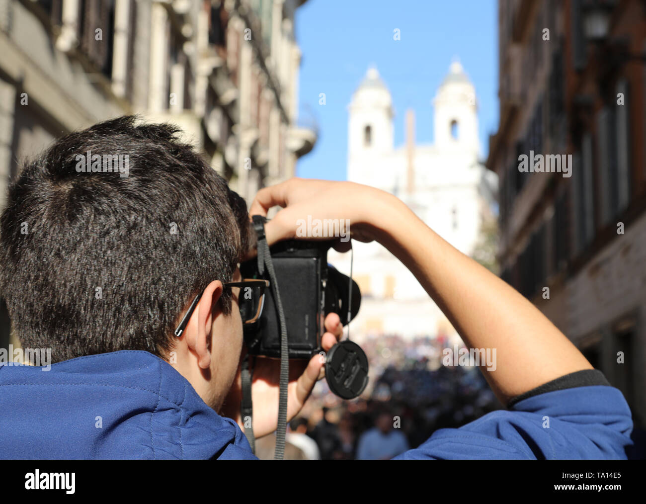 young photographer with digital camera in Via dei Condotti in Rome Italy and the church of the Trinity in the background - Stock Image