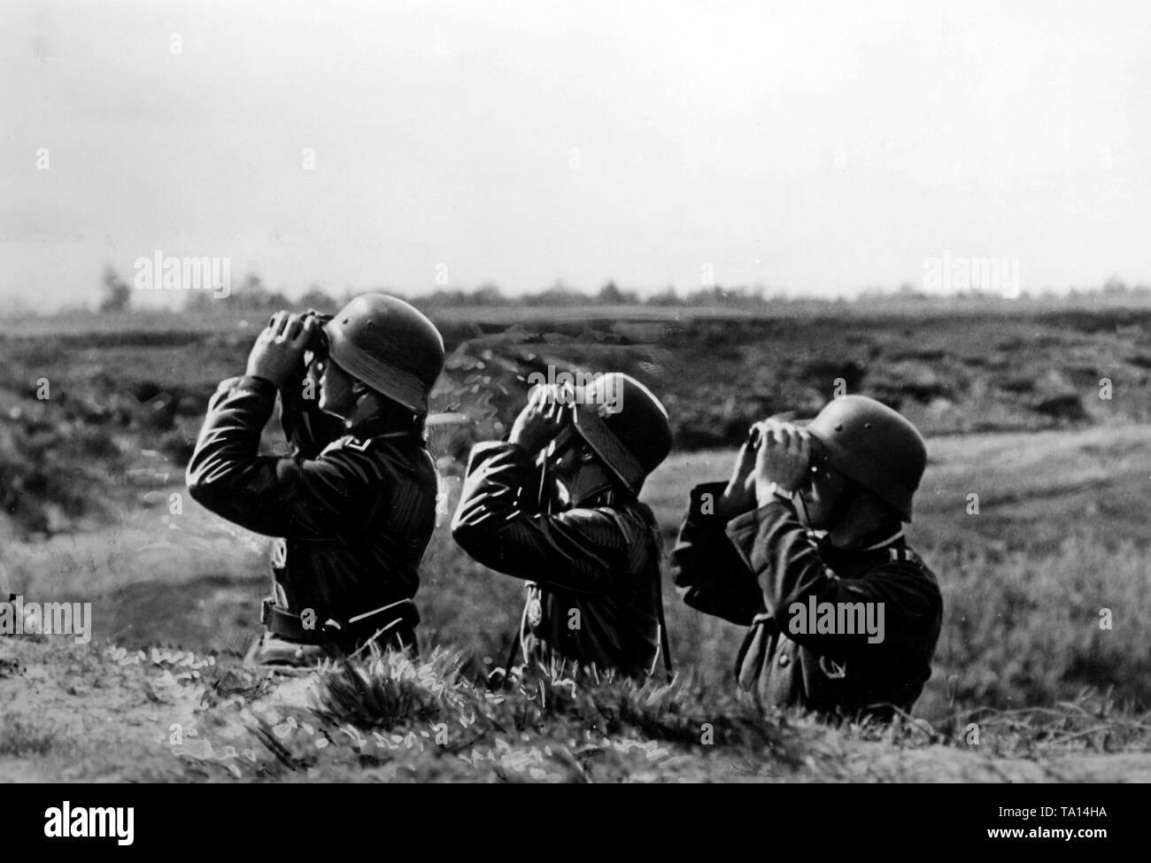 Infantrymen observe the Luftwaffe with binoculars during their deployment southeast of Lake Ilmen. Photo of the Propaganda Company (PK): war correspondent Etzold. - Stock Image