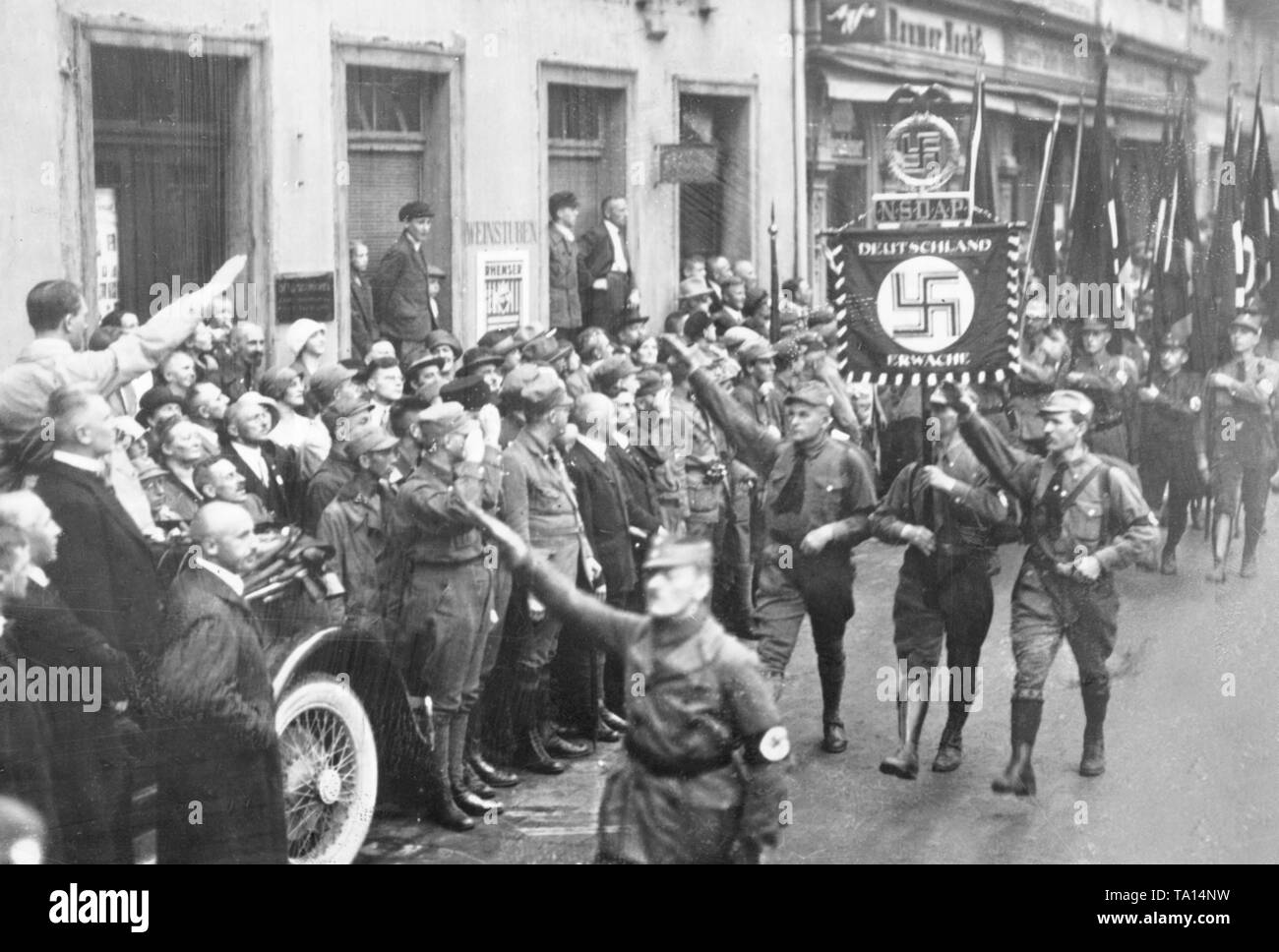 On the first party conference of the NSDAP in Weimar, the call of Dietrich Eckarts, 'Deutschland erwache' (Germany awake), becomes the slogan of the still young party. Adolf Hitler greets the standard bearers on his car, ahead stand the Franconian leader Julius Streicher, Gottfried Feder and Alfred Rosenberg. - Stock Image
