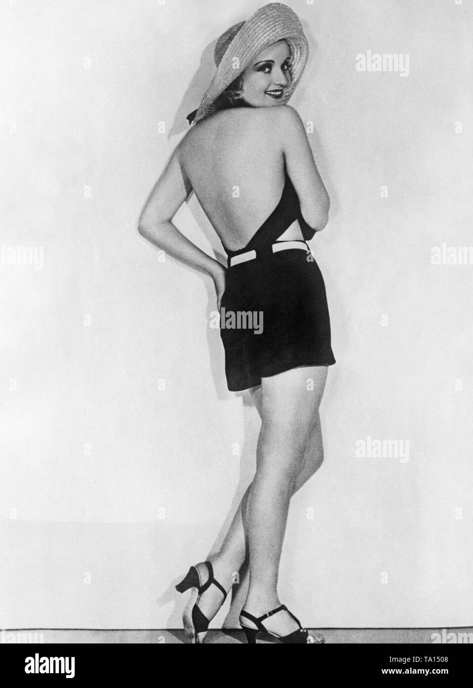 A woman posing in a 1930s style backless swimsuit. - Stock Image
