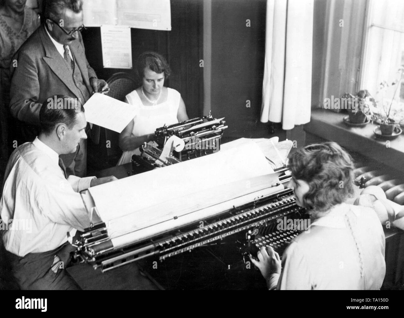 Counting votes at the Berlin electoral office on the occasion of the Reichstag election . Dr. Lohmann, head of the news office, is assisting the counting with his co-worker. In the foreground the largest counting machine in Europe. Stock Photo