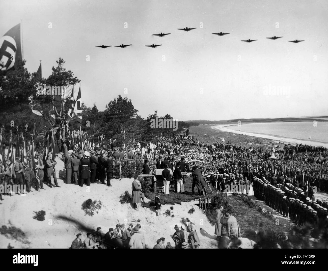 Groundbraking ceremony of the Baltic Sea beach resort of the Nazi organization 'Kraft durch Freude' ('Strength through Joy') between Binz and Sassnitz on Ruegen (today Prora) during an aerobatic maneuver of a flight of 9 aircrafts of the Luftwaffe (airforce). On the right, marines. - Stock Image