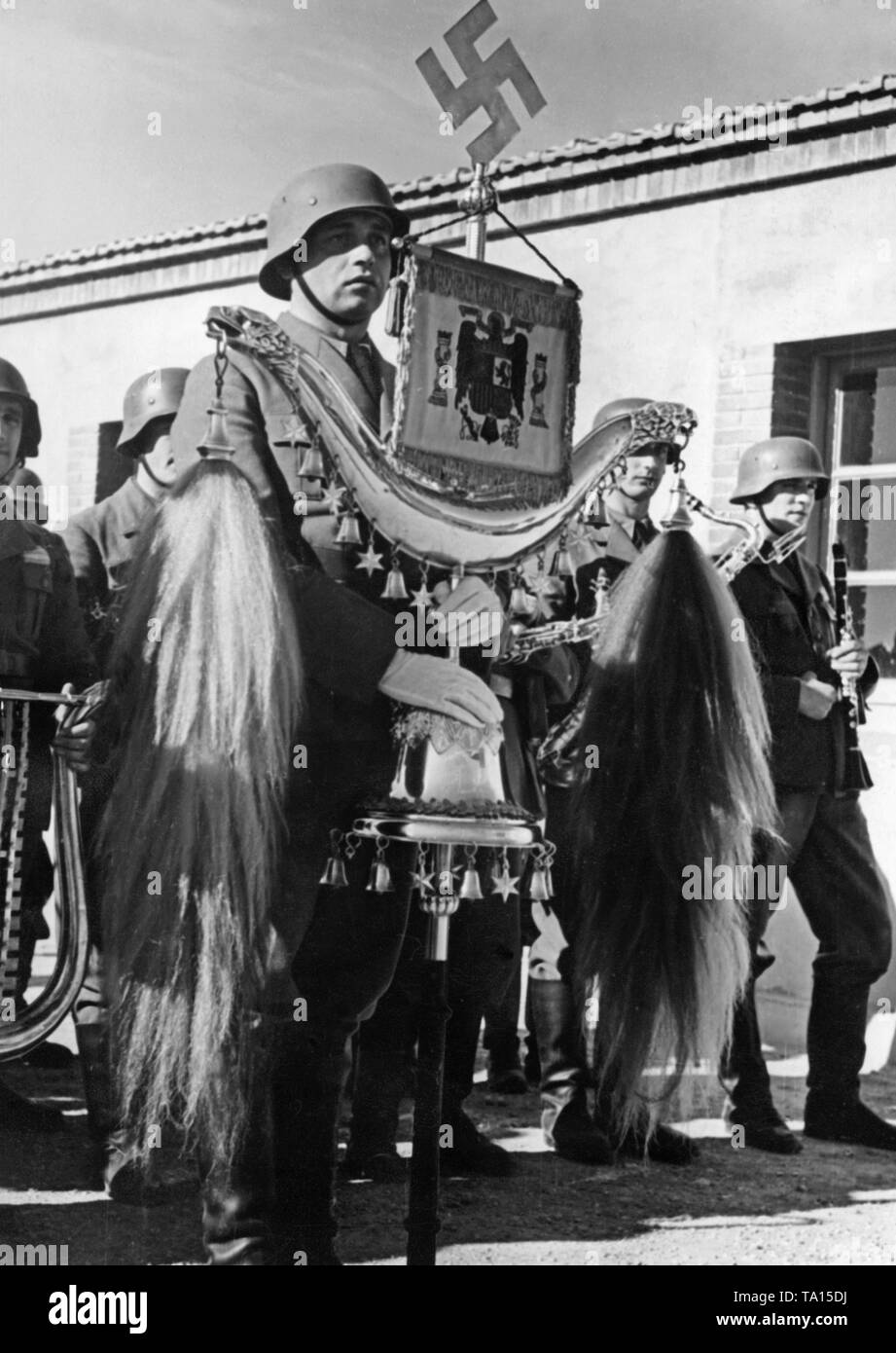 Photo of a member of the military band of the Condor Legion holding a Turkish crescent (decorated with a swastika and the Spanish national emblem) during the parade on the occasion of the celebration day of the Luftwaffe at the airfield of Saragossa, Aragon on March 1, 1939. - Stock Image