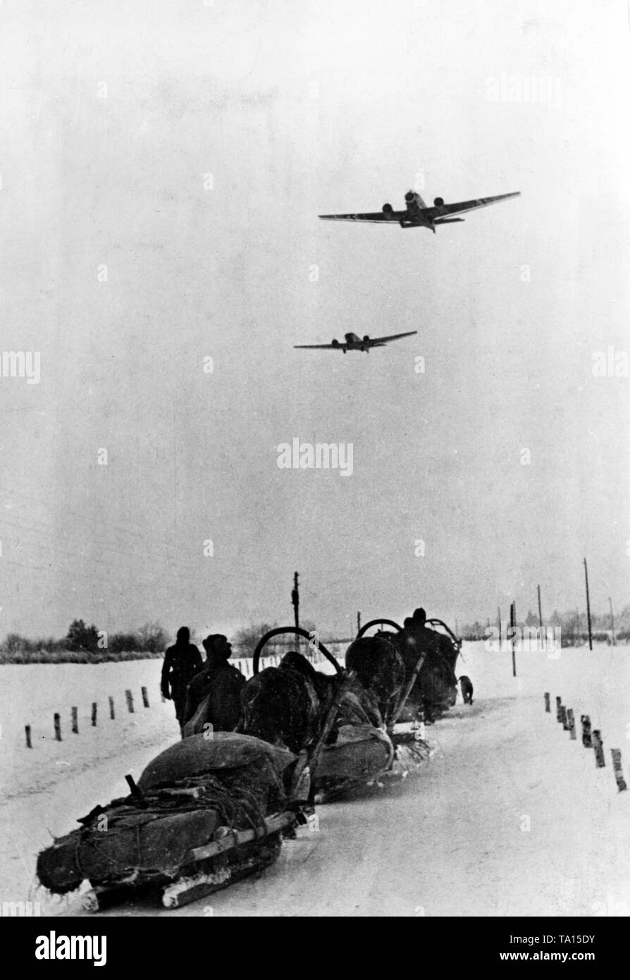 Two Junkers Ju 52 aircrafts cross German soldiers near Demjansk. The photo was taken in front of the complete encirclement and the associated airlift. Photo of the Propaganda Company (PK): war correspondent Beissel. - Stock Image