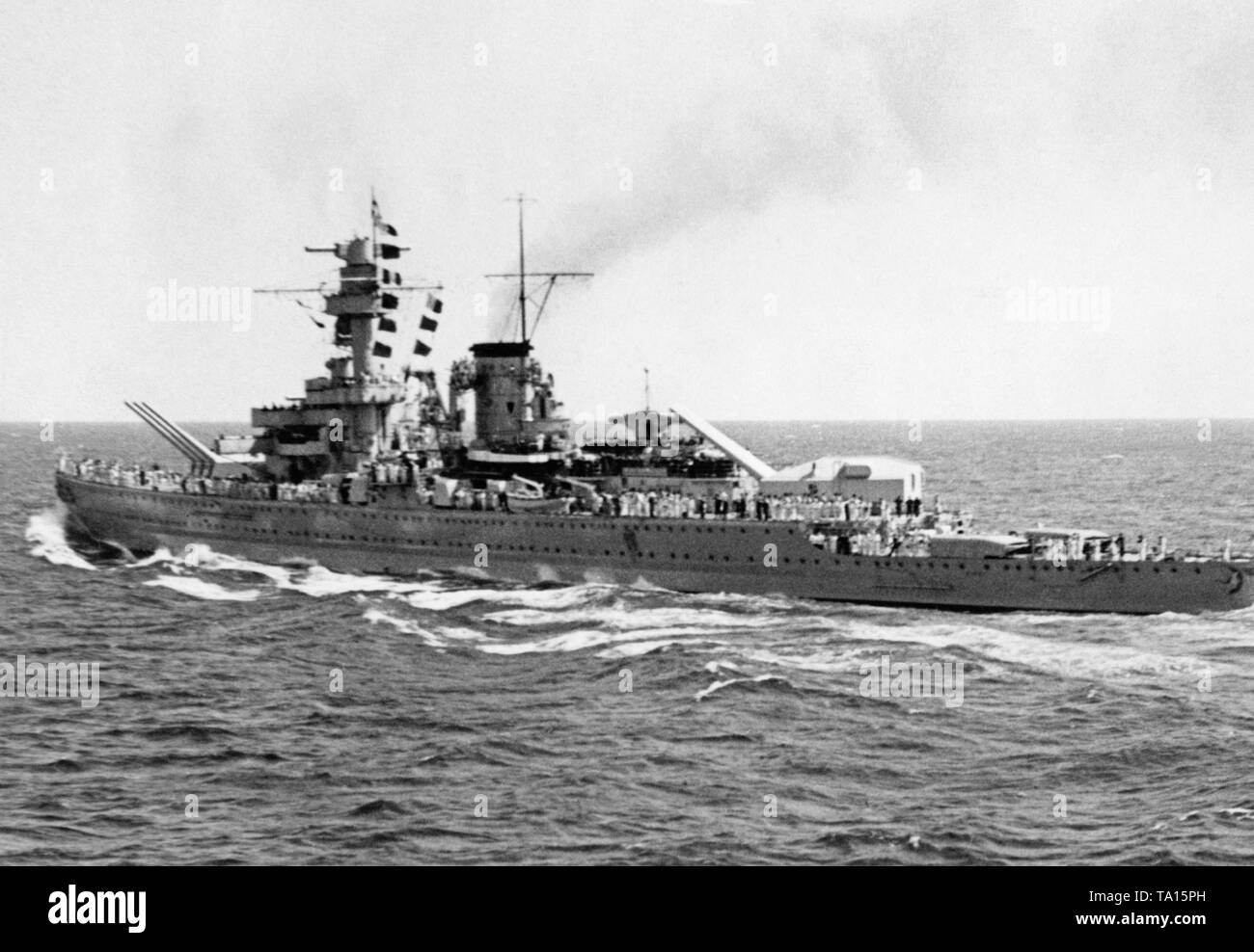 Photoof theheavy cruiser 'Deutschland' in a stormy sea during a trip abroad in 1935. The crew has lined up on the deck. The twoturrets with six 28 cm quick-fire guns at thebow and at therear. - Stock Image