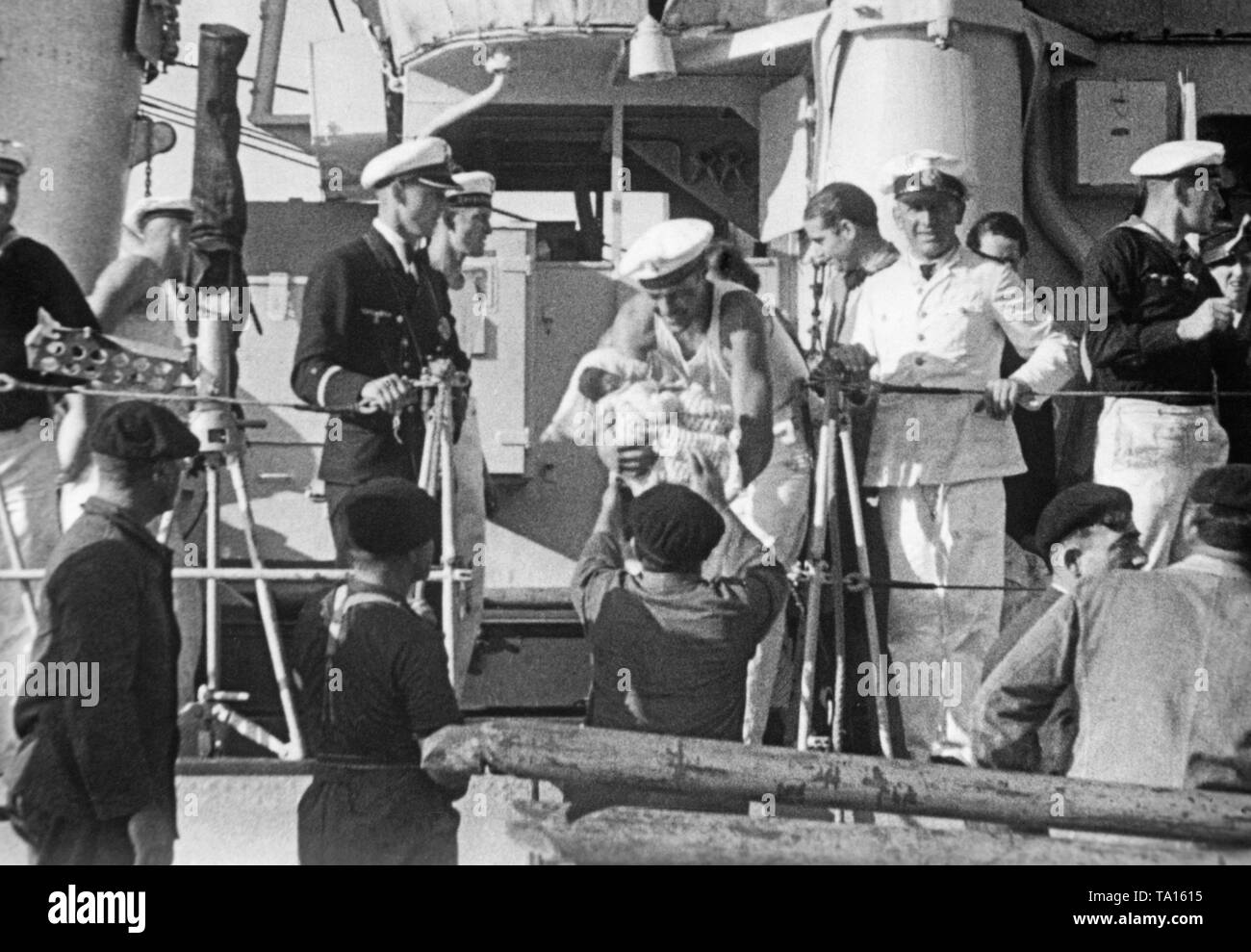 The German destroyers 'Jaguar' and 'Wolf' bring Spanish refugees to the port of St. Jean de Luz, French Basque country, France, during the Spanish Civil War on September 18, 1936. In the photo, a German sailor, who is handing over a baby from the deck. German naval officers are standing around the man taking the baby. - Stock Image
