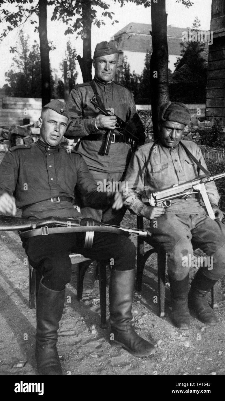 Three Russian soldiers posing for the camera in the captured Berlin. The soldier in the center and the man on the right are armed with German MP-40, a popular booty weapon among Russian soldiers. Stock Photo
