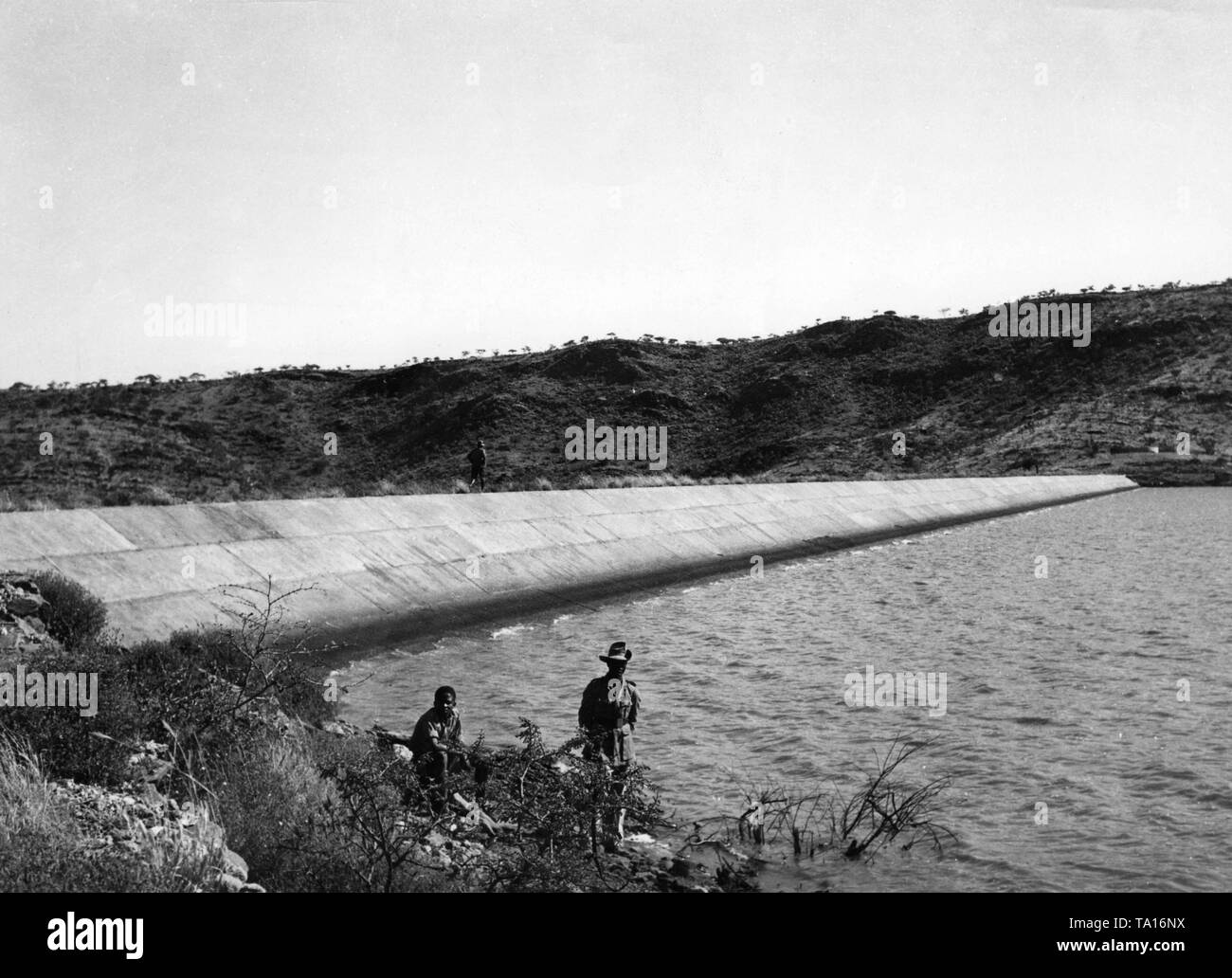 The inauguration of the reservoir near Windhoek, which was to ensure the drinking water supply of the state capital, took place in 1934. In the foreground are two guards in European clothes on the bank of the reservoir, the uniforms of the German Schutztruppe. - Stock Image