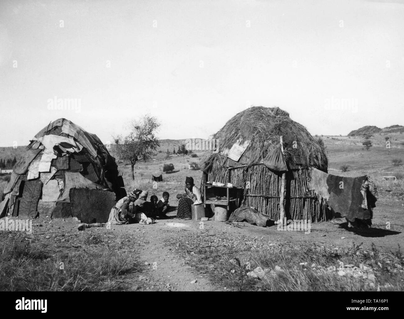 A group of children in European clothes sits between two pondoks in the former German South West Africa. The settlement is located in the Auesbergen on the grounds of a farm operated by Germans. - Stock Image