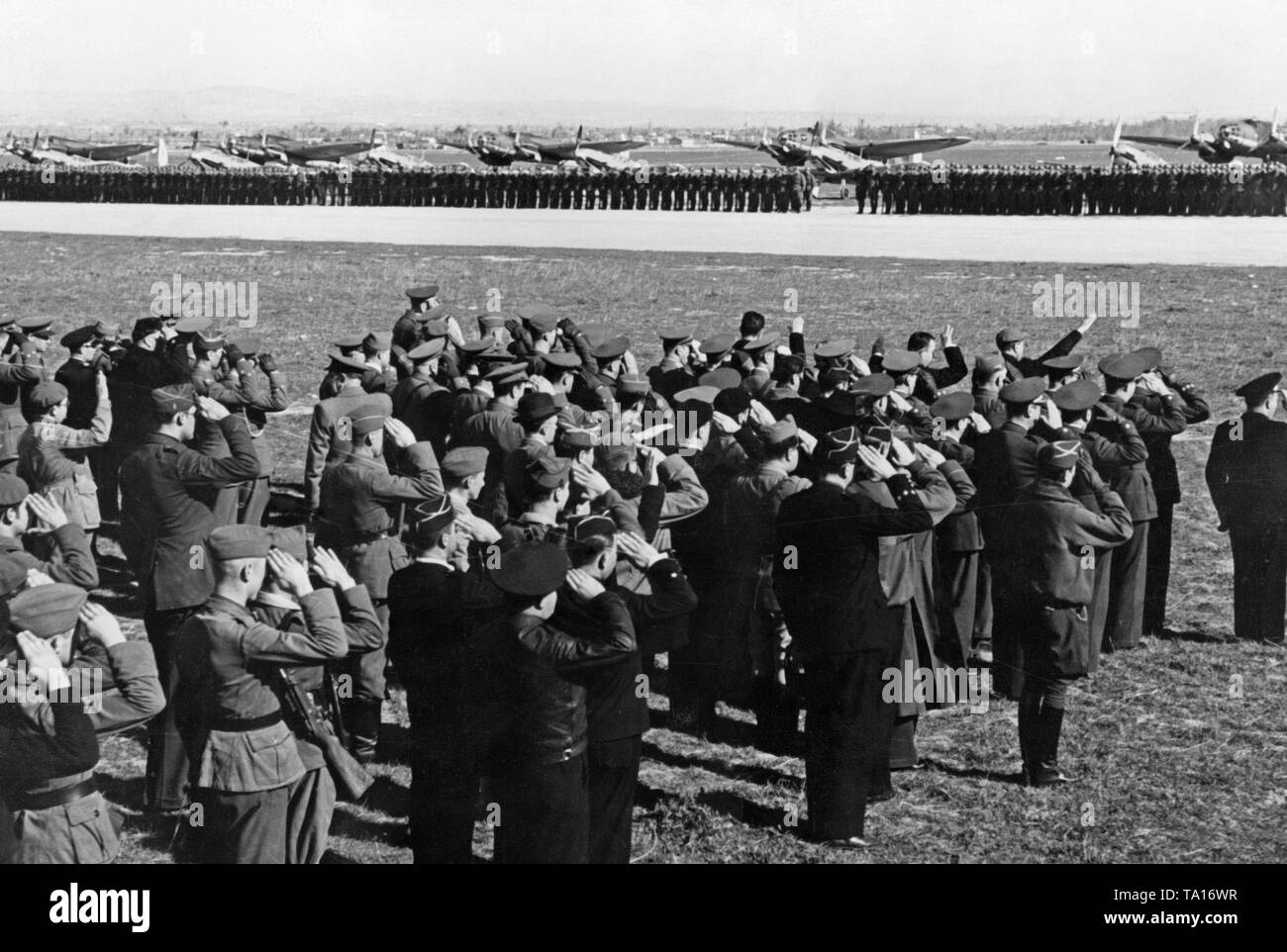 Photo of a parade of the Condor Legion on the airfield of Saragossa on the occasion of the Day of the Luftwaffe (airforce) on March the 1st, 1939. Soldiers have lined up on the airfield in the background. Behind, there are fighter aircrafts, type Messerschmitt Bf 109, and combat bombers, type Heinkel He 111. In the foreground German and Spanish soldiers are saluting. - Stock Image