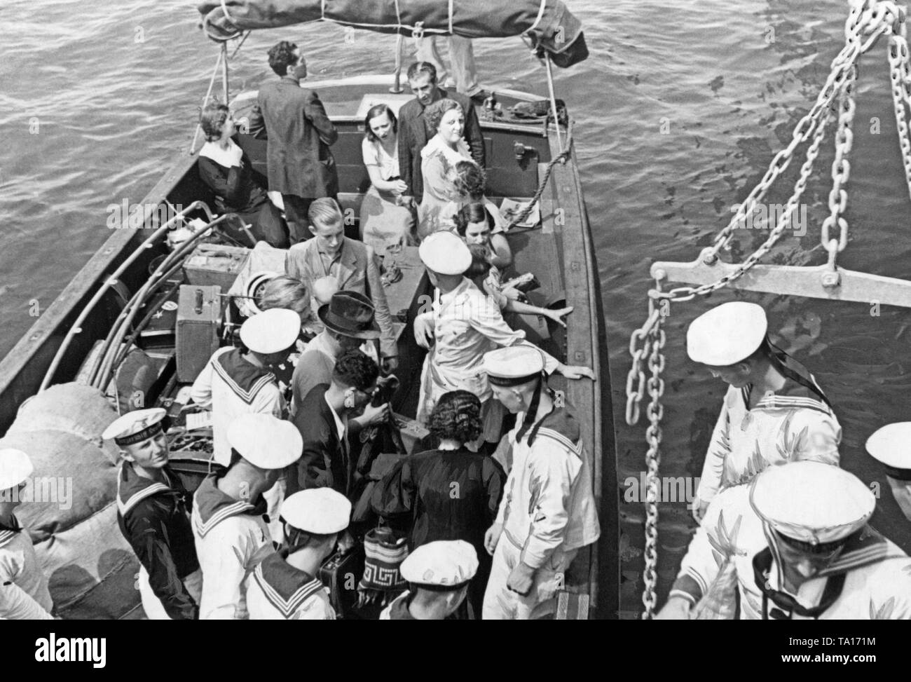 Photoof a group of German refugees during the Spanish Civil War in a dinghy of theheavy cruiser'Deutschland'at a roadsteadoff Valencia. A group of sailors and an officer help people come aboard 'Deutschland'. 'Deutschland'brought the refugees to Girona, where they were taken over by the steamer of the Nazi organization 'Kraft durch Freude' ('Strength through Joy'), Monte Sarmiento (launched in 1924, Monte-Klasse, sunk in 1942). - Stock Image