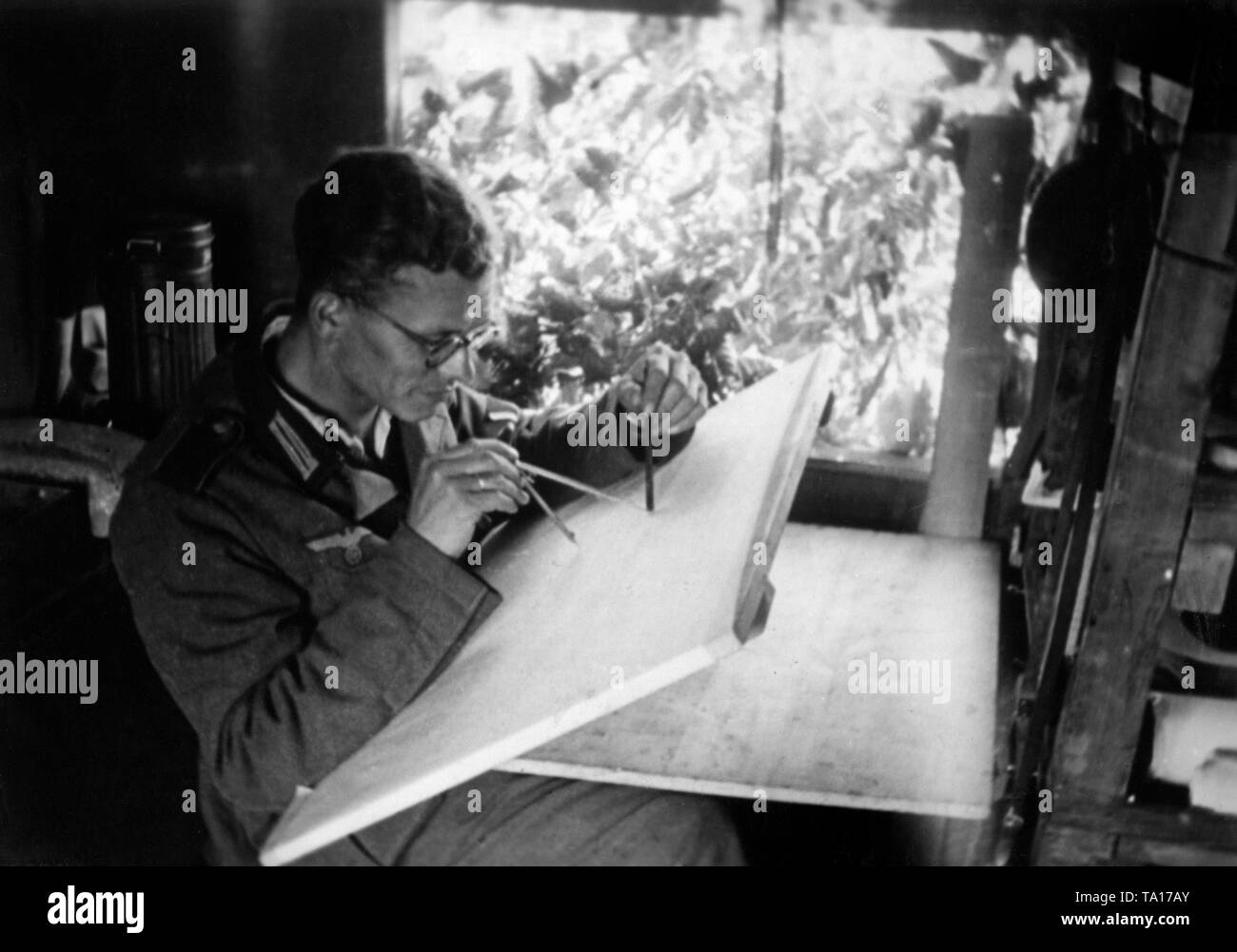 A soldier of a Korpskartenstelle (Corps Map Unit) draws new scout results into existing maps. Eastern Front, August 1941. Photo: war reporter Utecht. - Stock Image