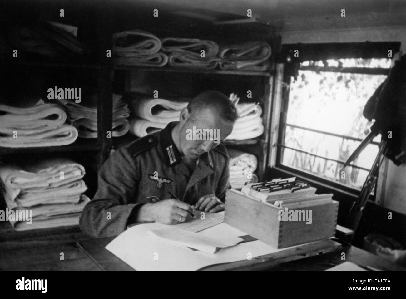 A member of the Wehrmacht arranges stocks of maps and records the maps on file cards. Photo: war reporter Utecht. Stock Photo