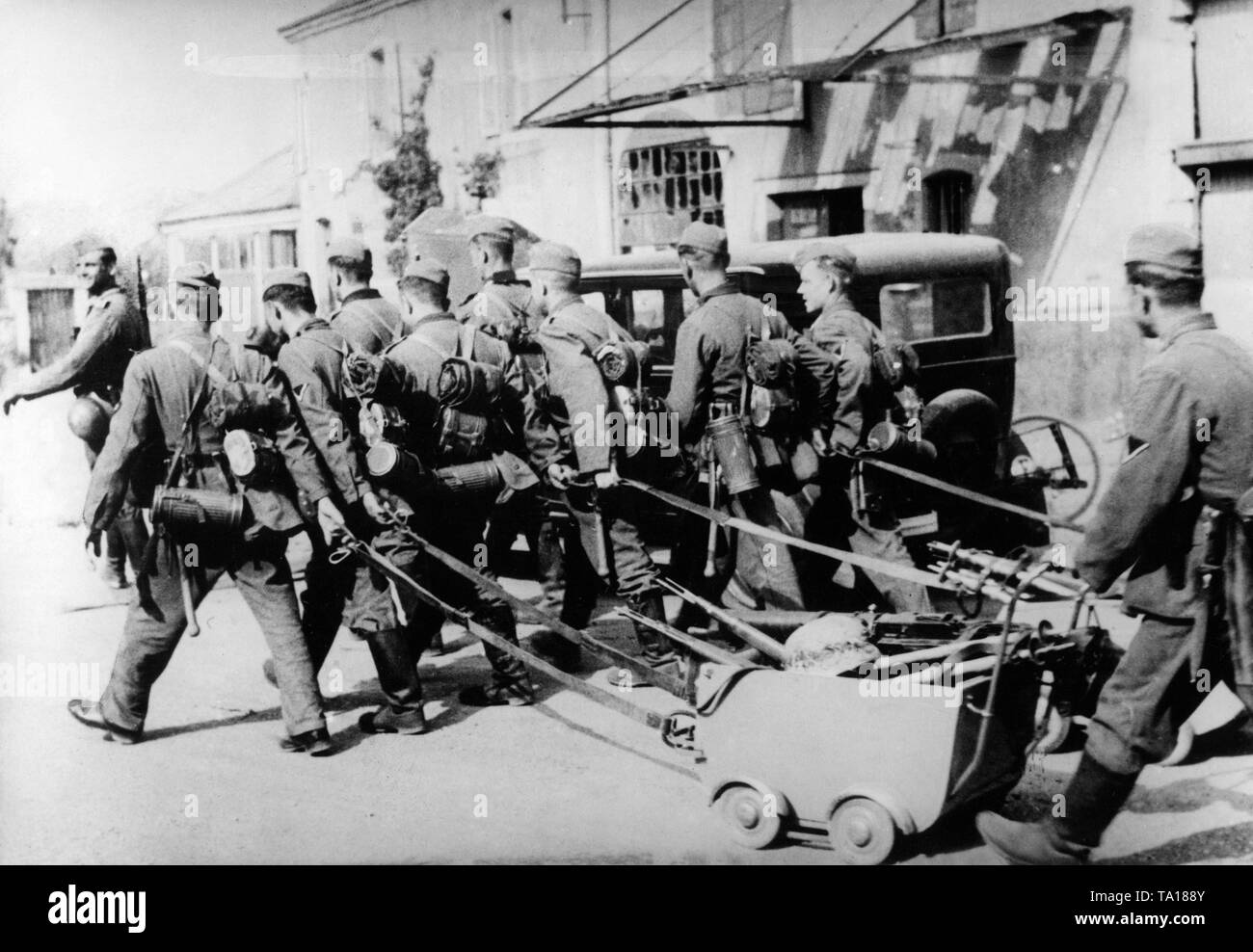 German infantry marching through a French village. They laid their rifles in confiscated strollers. Stock Photo