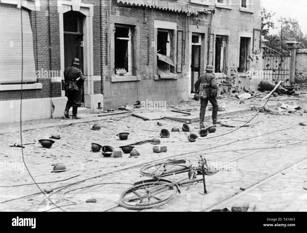 Two German infantrymen go through a French town. A dead horse and abandoned steel helmets testify the retreat of the French troops. Stock Photo